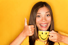 Woman drinking coffee happy thumbs up. Woman drinking coffee happy giving thumbs up smiling enjoying her morning coffee on yellow background. Beautiful young Royalty Free Stock Image