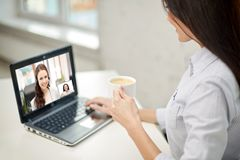 Woman drinking coffee having video call on laptop stock images