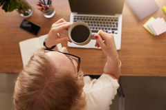 Woman drinking coffee at her desk. Royalty Free Stock Image