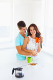 Woman drinking coffee and her husband hugging her Stock Photography