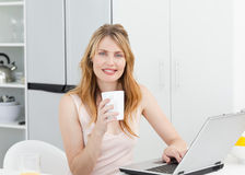 Woman drinking coffee in her kitchen Royalty Free Stock Image