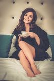 Woman drinking coffee in a hotel room Stock Image