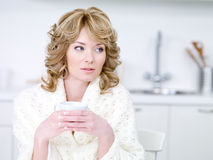 Woman drinking coffee in the kitchen Royalty Free Stock Image