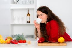 Woman is drinking coffee in the kitchen Stock Photography