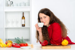 Woman is drinking coffee in the kitchen Royalty Free Stock Photo