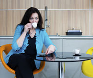 Woman drinking coffee in kitchen Stock Image