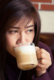 Woman drinking a coffee latte. In cafe Stock Photo