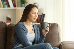 Woman drinking coffee and looking away on a couch. Serious woman drinking coffee and looking away through a window sitting on a couch in the living room at home stock image