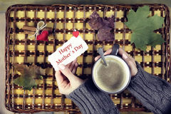 Woman drinking coffee and looking at the card mother s day Stock Photo