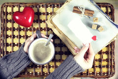 Woman drinking coffee and looking at the card Valentine`s Day Stock Image