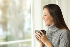 Woman drinking coffee looking outside through a window royalty free stock photos