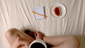 Woman is drinking coffee and making plans on day, top view hd video. Girl is drinking coffee and making plans on day, top view hd video stock footage