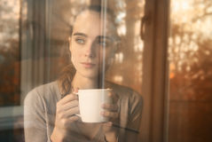 Woman drinking coffee in the morning sitting by th stock image