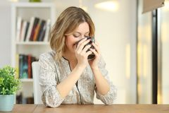 Woman drinking coffee from a mug at home. Happy woman drinking coffee from a mug on a table at home royalty free stock images