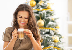 Woman drinking coffee near christmas tree Royalty Free Stock Photos
