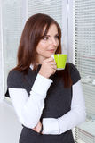 Woman drinking coffee near the window smiling Royalty Free Stock Image