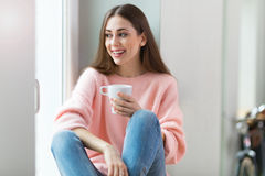 Woman drinking coffee near window Stock Photography