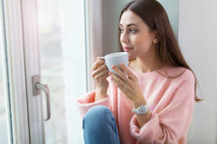 Woman drinking coffee near window Royalty Free Stock Photos