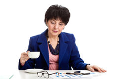 Woman drinking coffee in office Stock Images