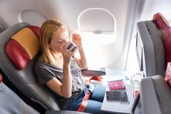 Woman Drinking Coffee On Commercial Passengers Airplane During Flight. Royalty Free Stock Photography