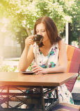 Woman drinking coffee at open-air cafe Stock Images