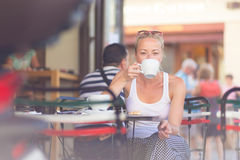 Woman drinking coffee outdoor on street. Royalty Free Stock Photo
