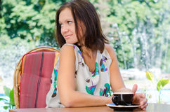 Woman drinking coffee outdoors. Woman seated at a garden table drinking coffee outdoors and looking to her right over her shoulder off frame Stock Image
