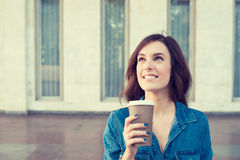 Woman drinking coffee outdoors holding paper cup stock photography