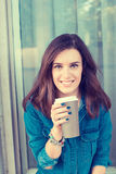 Woman drinking coffee outdoors holding paper cup stock image