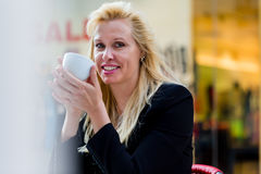Woman drinking coffee outside in city cafe Stock Photo