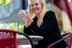Woman drinking coffee outside in city cafe Stock Image