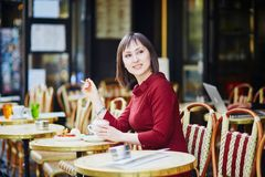 Woman drinking coffee in Parisian outdoor cafe Stock Image