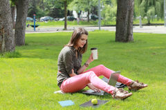 Woman Drinking Coffee in a Park. Young student woman drinking coffee while studying on a bech in an urban park Royalty Free Stock Photos