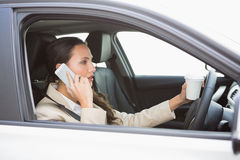 Woman drinking coffee on phone while driving Stock Photos