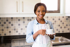 Woman drinking coffee. Pretty african woman drinking coffee in kitchen Stock Photos