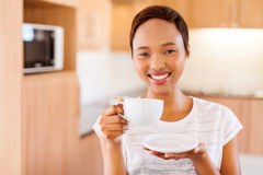 Woman drinking coffee. Pretty young african woman drinking coffee in kitchen Royalty Free Stock Images