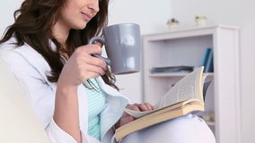 Woman drinking a coffee while she is reading stock video footage