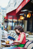 Woman drinking coffee and reading a book in cafe Royalty Free Stock Image