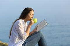 Woman drinking coffee and reading a book outdoors. Side view of a woman drinking coffee and reading a book outdoors on the beach Royalty Free Stock Images