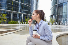 Woman drinking coffee and reading her touchscre Royalty Free Stock Images