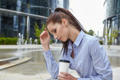 Woman drinking coffee and reading her touchscre Stock Image