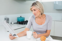 Woman drinking coffee while reading newspaper in kitchen Stock Photos
