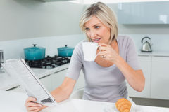 Woman drinking coffee while reading newspaper in kitchen Royalty Free Stock Photos