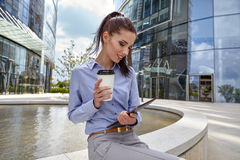 Woman drinking coffee and reading tablet Royalty Free Stock Image