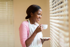 Woman drinking coffee. Relaxed young african woman drinking coffee near the window Stock Photo