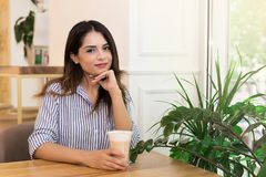 Woman drinking coffee, relaxing in cafe sitting near the window royalty free stock photo