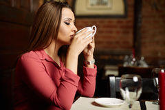 Woman drinking coffee in a restaurant Stock Photography