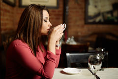 Woman drinking coffee in a restaurant Stock Image