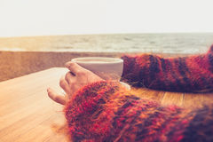 Woman drinking coffee by the sea. Woman in a red woolen jumper drinking coffee on a cold day Stock Photos