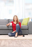 Woman drinking coffee seated by a modern sofa Stock Photos